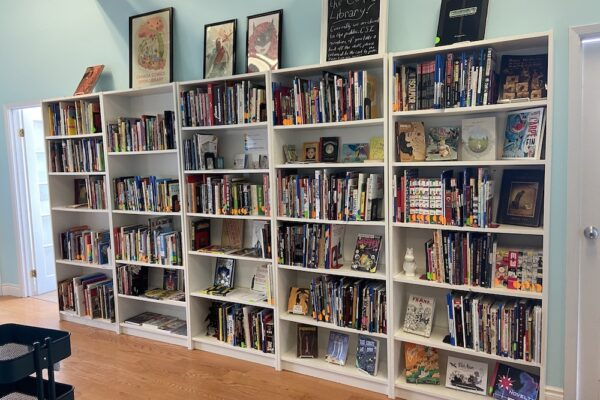 """A sneak peek at our new cozy space on the 4th floor of @csitoronto Annex! Lots of colourful comics on tall white shelves surrounded by light blue walls, with several larger comics displayed on top of the shelves along with framed artwork and a chalkboard sign that reads """"Welcome to the comics library!"""""""